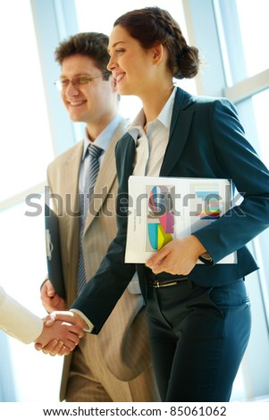 Photo of successful woman handshaking with partner after striking deal at meeting