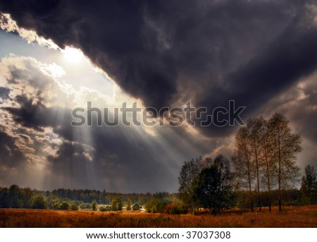 Photo of sunset sky with rays of light over field