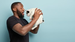 Photo of surprised black bearded man holds small pet in air, finds out about disease, brings dog to veterinary clinic for advice, keeps mouth opened, prepares animal for routine ear check by vet