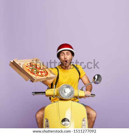 Photo of surprised man in yellow t shirt and protective headgear, carries rucksack, holds fresh baked pizza in carton box, tries to avoid traffic jams, drives fast in rush, isolated over purple wall