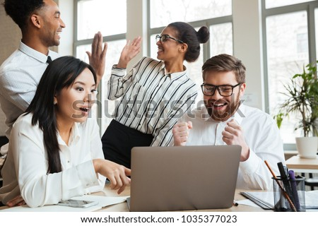 Photo of surprised screaming young business colleagues indoors coworking. Looking aside using laptop computer.