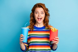 Photo of surprised shiny ginger woman wear colorful sweater holding soda cup french fries isolated blue color background