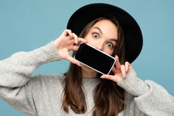 Photo of surprised shocked amazed Beautiful positive young female person wearing black hat and grey sweater holding mobilephone showing smartphone isolated on background looking at camera