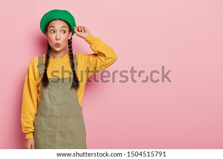 Photo of surprised young Asian woman with rounded lips, minimal makeup touches beret and looks aside in astonishment, poses against pink background, blank space for your advert, wears two pigtails