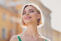 Photo of sweet adorable young lady wear green outfit smiling walking closed eyes enjoying sunshine outside urban city street