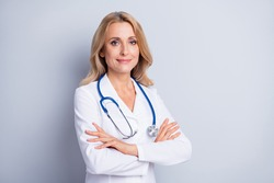 Photo of sweet confident mature lady doctor wear white coat arms crossed empty space isolated grey color background