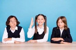 Photo of sweet doubtful schoolkids formalwear smiling sitting table arms folded looking for answer isolated blue color background