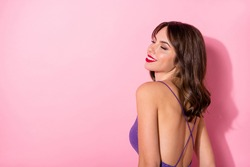 Photo of sweet dreamy young woman dressed violet dress showing necked back empty space isolated pastel pink color background