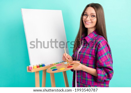 Photo of sweet straight hairdo young lady painting wear spectacles checkered shirt isolated on vivid teal color background
