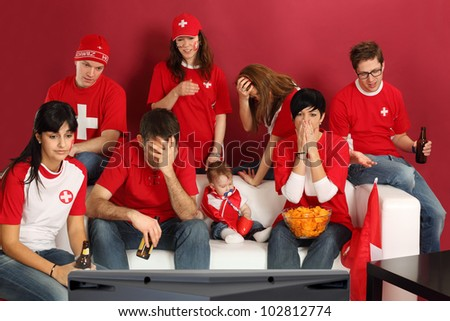 Photo of Swiss sports fans watching television and being disappointed with the game.