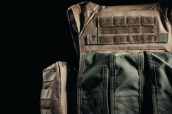Photo of tactical military soldier armored vest with pouches close-up view on dark background.
