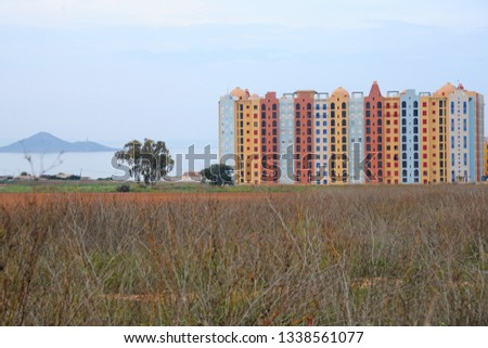 photo of tall colored buildings and the beach on a natural spit of La Manga between the Mediterranean and the Mar Menor, Cartagena, Costa Blanca, Spain
