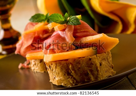 photo of tasty bread slices with bacon and melon - stock photo