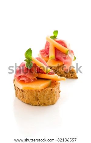 photo of tasty bread slices with bacon and melon on isolated background