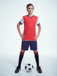 Photo of teen boy in sportswear holding soccer ball - posing at studio. Full portrait.