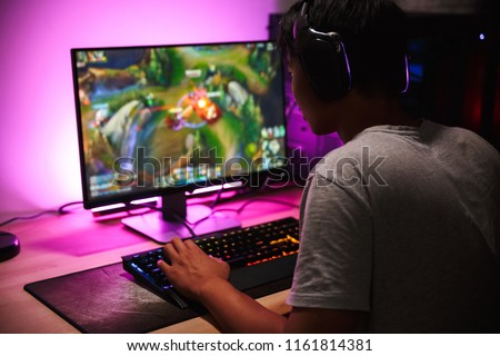 Photo of teenage gamer boy playing video games on computer in dark room wearing headphones and using backlit colorful keyboard