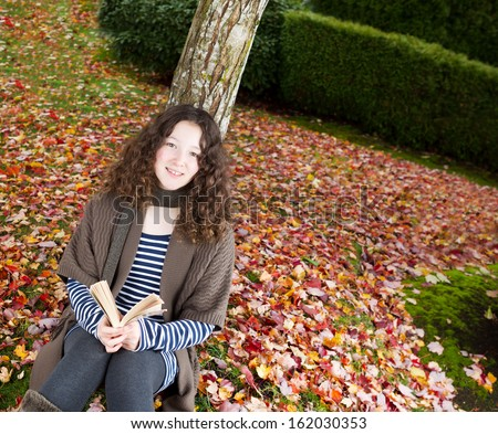 Photo of teenage girl, looking forward, enjoying her book while lying against a tree during the autumn season dressed in earth colors