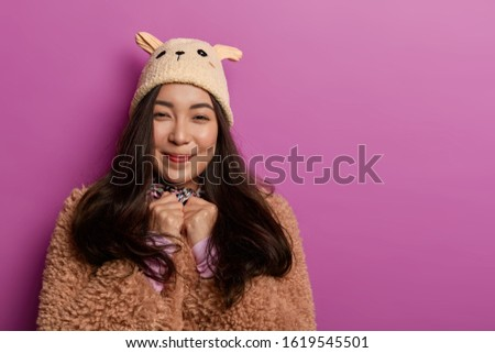Photo of teenage girl wears fashionable hat and brown coat, looks sincerely with gentle smile, enjoys wearing new outfit, isolated over lilac background, copy space area for your promotion or text