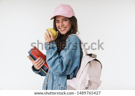 Photo of teenage student girl wearing cap smiling while holding green apple and studying books isolated over white background #1489765427