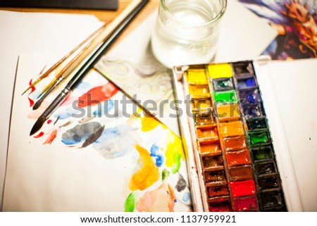 photo of the artist illustrator workbench table with watercolors, water, brushes, paper, palette top view #1137959921