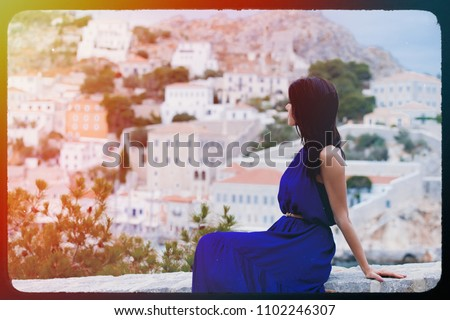 photo of the beautiful young woman sitting on the stone railing and looking at the splendid view in Greece . Image made with old film frame. Zdjęcia stock ©