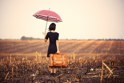 photo of the beautiful young woman with suitcase and umbrella standing in the middle of the field
