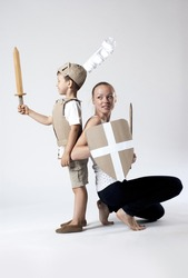 photo of the boy in medieval knight costume made of cardboards with his mother