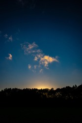 Photo of the evening sky at sunset with the sihouette of a tree line and small clouds
