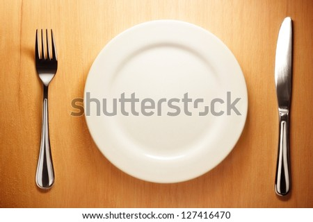 Photo of the fork and knife with white plate on wooden background