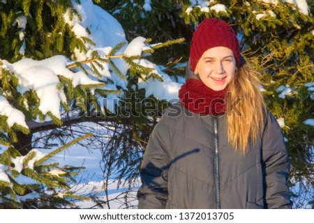 Photo of the girl on the background of snowy fir paws. Fluffy snow. red knitted hat. it's cold outside