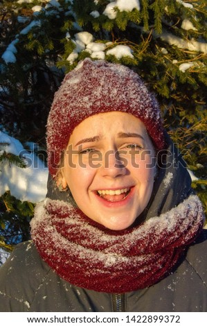 Photo of the girl on the background of snowy fir paws. Fluffy snow. red knitted hat. it's cold outside #1422899372