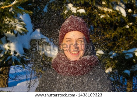 Photo of the girl on the background of snowy fir paws. Fluffy snow. red knitted hat. it