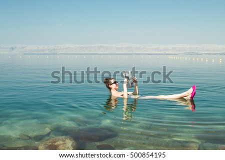Photo of the Girl reading newspaper floating on surface Dead Sea enjoy summer sun and vacation. Recreation tourism, healthy lifestyle, free time concept #500854195