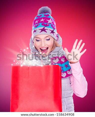 Photo of the happy surprised woman with gifts after shopping to the new year at shop