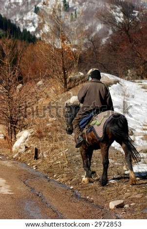 Photo of the horseman in mountain area during early spring