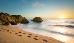 Photo of the pebble beach of Cowell Ranch near Half Moon Bay on the California coast.  Sunset scene with ocean waves and footprint walking across the beach.