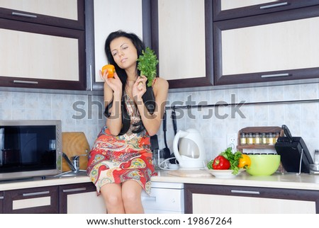 Photo of the pretty lady in the kitchen preparing salad