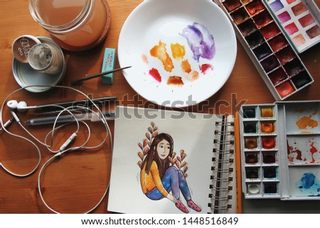 Photo of the sketchbook, watercolors, plate, brushes and headphones on the wooden table