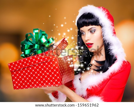 Photo of the surprised  snow maiden looks into the christmas box  with gift in it -  over creative background