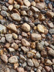 Photo of the texture of a stone path from stones laid out to the water, stone background, texture of a stone floor. The road is made of small and large brown stones.