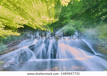 Photo of the waterfall, taken at a long shutter speed with a change in focal length. Abstract drawing.Blurred water flow, sunlight, lots of greenery around. #1489847735