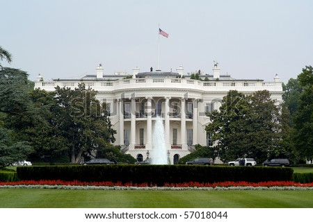 Photo of The White House in Washington DC taken from the street with a clear blue sky.  Includes landscape and fountain.