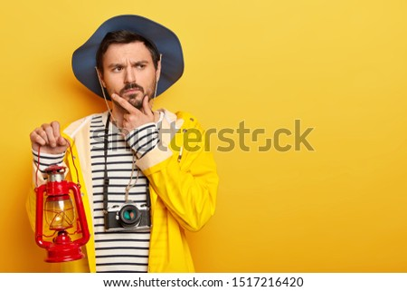 Photo of thoughtful man holds chin, thinks about having journey or expedition, holds little gas lamp, dressed in raincoat, headgear, uses camera for making photos, isolated over yellow background