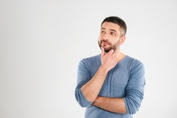 Photo of thoughtful man isolated over white background wall. Looking aside.