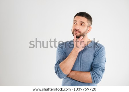 Photo of thoughtful man isolated over white background wall. Looking aside. #1039759720
