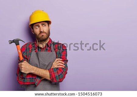 Photo of thoughtful tired mannual worker holds hammer, keeps arms crossed over chest, thinks about what to repair, wears yellow protective headgear, shirt with apron, copy space on purple background
