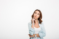 Photo of thoughtful young woman standing isolated over white wall background. Looking aside.