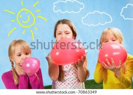 Photo of three cute girls inflating balloons