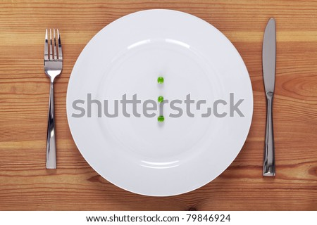 Photo of three green peas on a white plate with knife and fork on a rustic wooden table.
