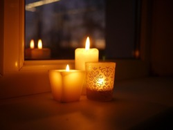 Photo of three lit candles - two paraffin wax candles and one tealight in a glass candle holder with glittery golden ornament, standing on a windowsill late in the evening.